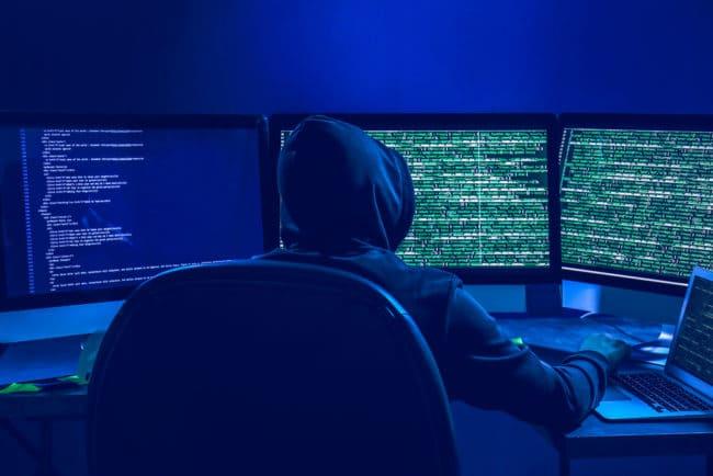 Website Hacker using computer in dark room