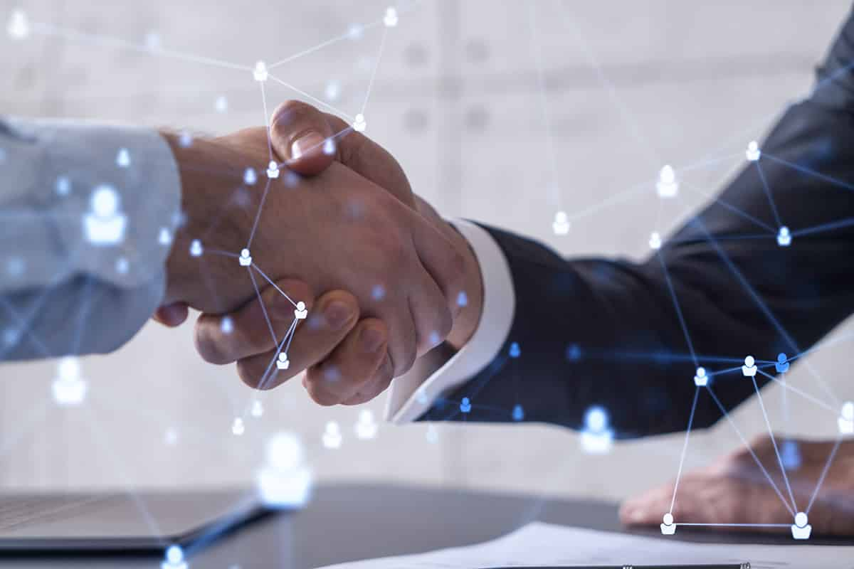 Recruitment concept to hiring of a new talented specialists for international company. Handshake to sign in of employment agreement. Social media hologram icons over the table with documents